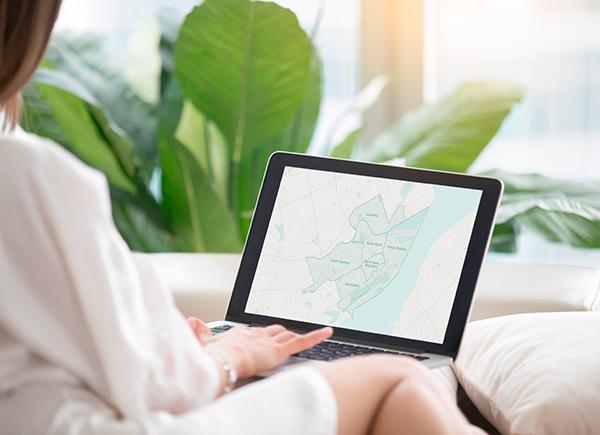Femme assise de dos de manière décontractée en train de faire une recherche sur son ordinateur portable.