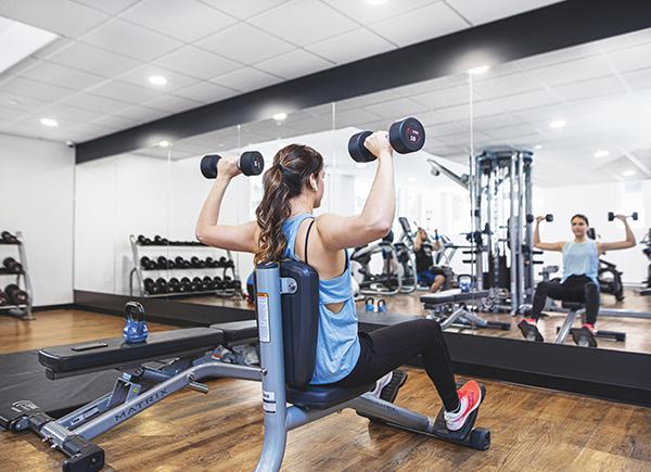 Femme en train de s'entraîner avec des poids dans un gym devant un miroir.