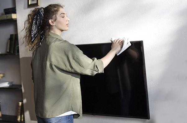 Grand ménage du printemps : une femme passe un linge sur son téléviseur dans son salon.