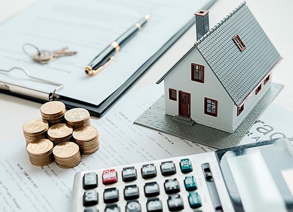 Représentation de la notion de capacité à payer. Modèle réduit d'une maison, monnaie, calculatrice, documents, crayon et clés.