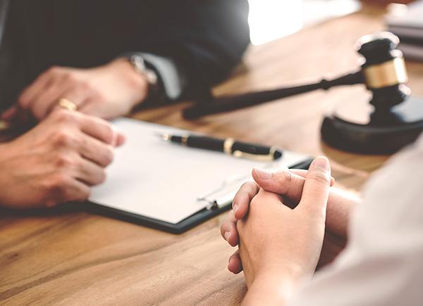 Mains d'homme et femme assis de chaque côté d'un bureau avec des documents entre eux et un maillet de juge.