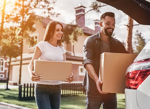 Un jeune couple place des boîtes en carton dans le coffre de la voiture le jour du déménagement.