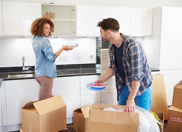 Un jeune couple défait les boîtes de déménagement de la cuisine.
