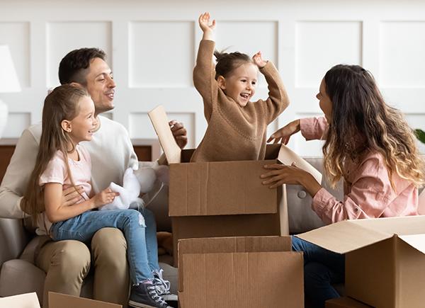 Une fillette sort d'une boîte de déménagement entourée de sa famille.
