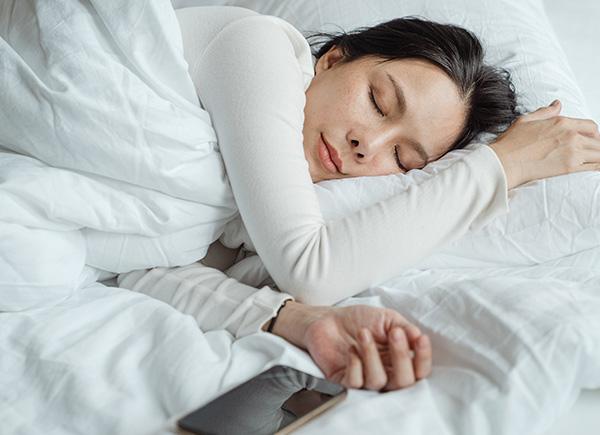 Jeune femme paisiblement endormie dans un lit entièrement couvert de literie blanche.