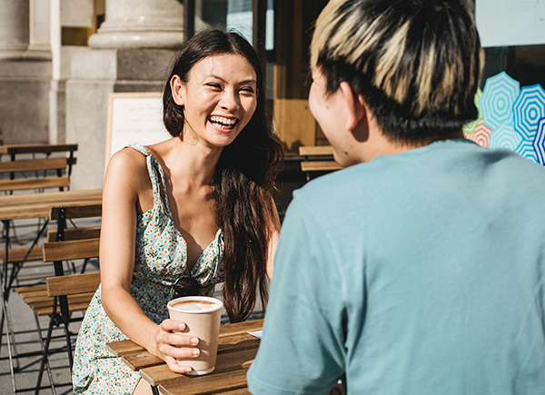 Jeune couple souriant assis face à face à une petite table à café dehors.