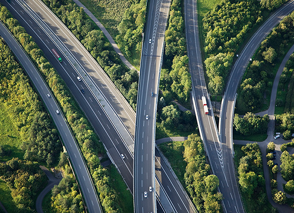 Vue aérienne de grands axes routiers entourés de verdure.