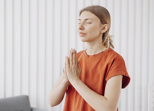 Jeune femme habillée d'un t-shirt orange en train de méditer les yeux fermés et les mains en prière.