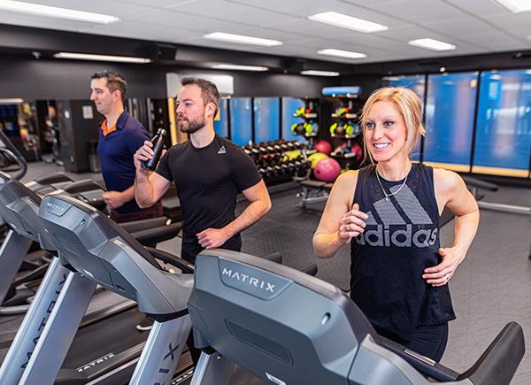 Bonnes habitudes de vie : Deux hommes et une femme en train de s'entraîner sur les tapis roulants au gym de l'Aventura.