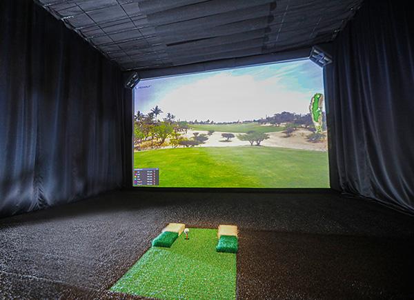 La salle de golf virtuel sans joueur, avec le grand écran présentant un terrain de golf et le point de départ.