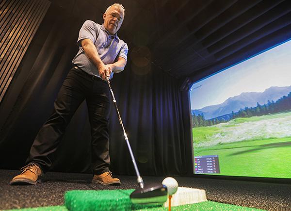 Un joueur de golf se préparant à effectuer un coup pendant une partie de golf virtuel.