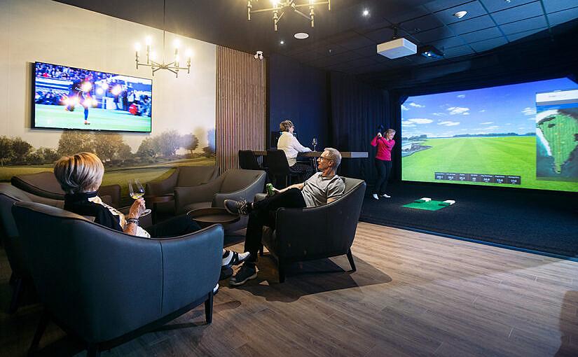 Quatre personnes dans le salon de golf virtuel de la Société immobilière Huot, dont deux sont assises sur des fauteuils.