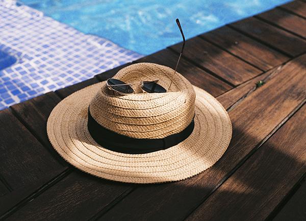 Chapeau de paille et lunettes de soleil déposés sur une table en bois au bord d'une piscine.