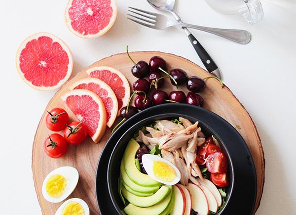 Une appétissante salade avec poulet, œuf, avocat et tomate, accompagnée de cerises et de pamplemousse.