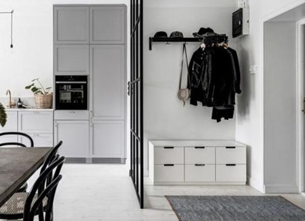 Astuces pour se sentir bien chez soi : Un petit hall d'entrée aménagé avec crochet au mur et meuble bas de rangement.