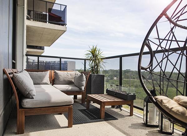 Astuces pour se sentir bien chez soi : aménager son balcon avec fauteuils, table basse, plantes et lumières d'ambiance.