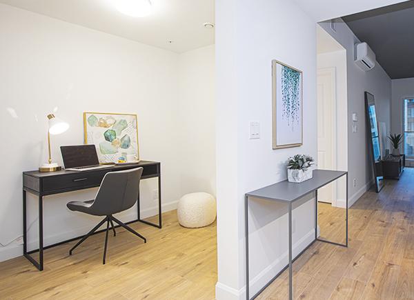 Logement avec un espace bureau pour accueillir une table de travail, une chaise, un pouf et un ordinateur portable.