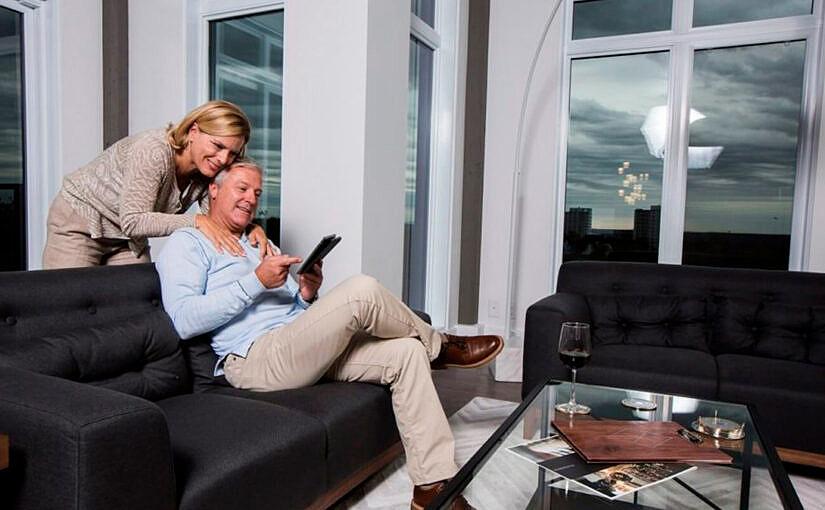 Couple dans la cinquantaine, heureux, dans le salon de leur condo moderne.