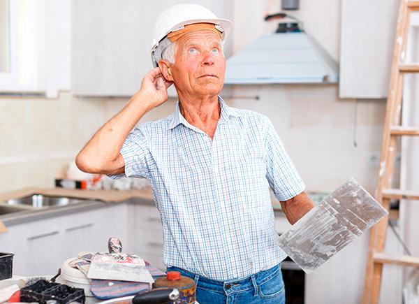 Homme âgé qui effectue des travaux de rénovation dans sa cuisine.