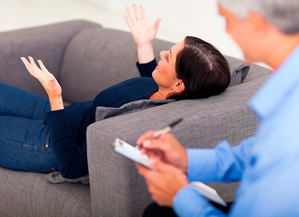 Femme sur un divan, dos à son thérapeute, pendant une consultation psychologique.