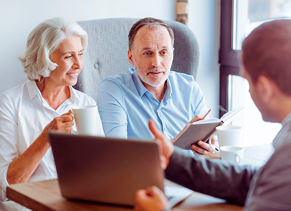 Un couple discute avec un planificateur financier pour savoir s'ils doivent acheter ou louer un condo pour la retraite.