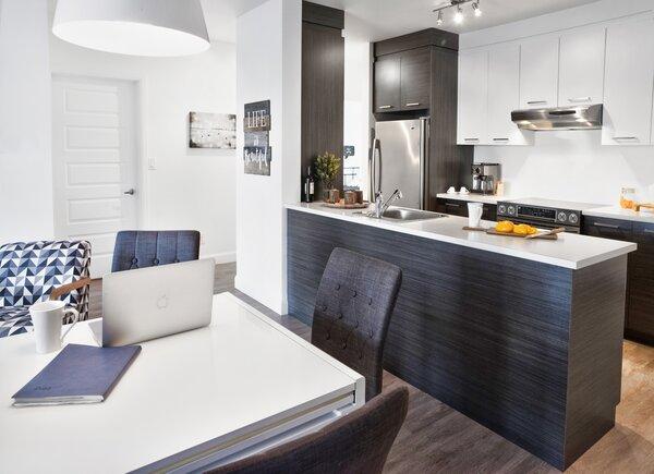 Cuisine et salle à manger à aires ouvertes dans un condo locatif des Diplomates.